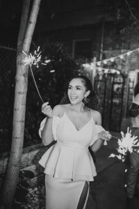 black and white woman holding #20 sparkler and smiling